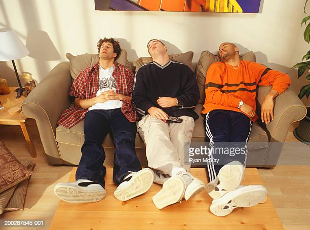 Three young men asleep side by side on sofa in flat
