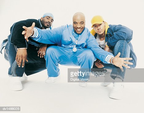 Three Young Men Crouching and Looking at Camera