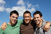 Three young men embracing outdoors, portrait, upper half