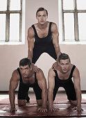 Three young men forming human pyramid