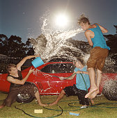 Three young men having water fight beside car