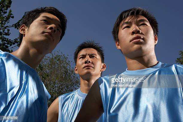 Three young men in blue jerseys look into the distance, shot from below.