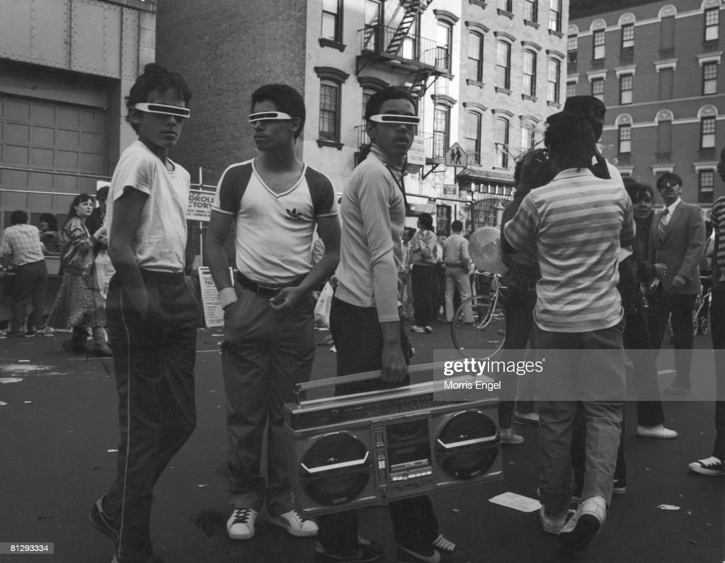 Three young men in robot sunglasses walk along a crowded street with a large boom box personal radio in hand, New York, New York, 1980s.