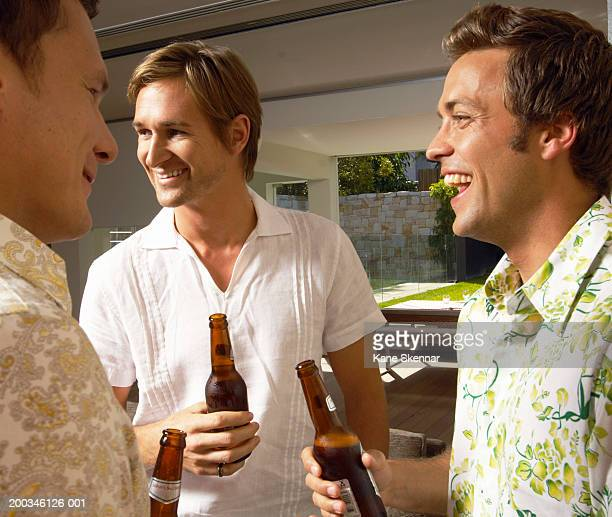 Three young men laughing and drinking beer, close up