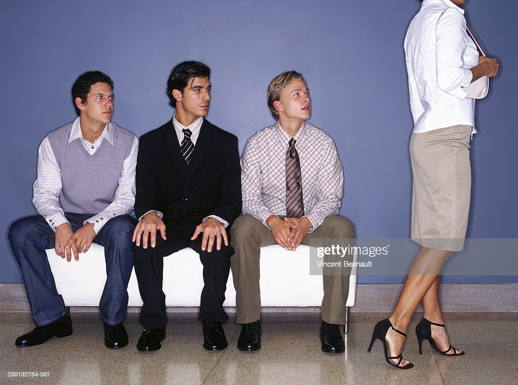 Three young men on bench indoors watching woman walking past : Stock Photo