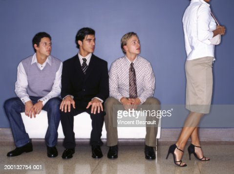Three young men on bench indoors watching woman walking past