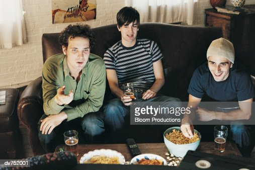 four men on a couch watching television stock photo getty images 1