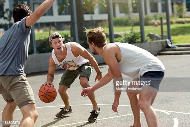 three young men playing basketball