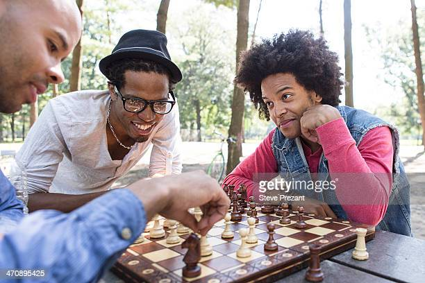Three young men playing chess in park