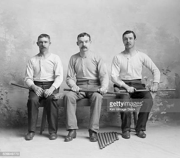 Three young men pose with the sledge hammers and industrial chisels for a studio portrait at the turn of the 20th century