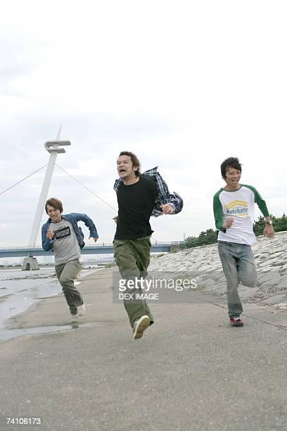 Three young men running near a river