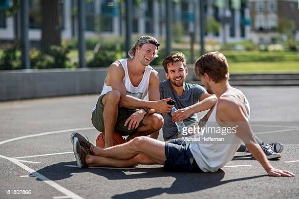 three young men sitting in basketball court