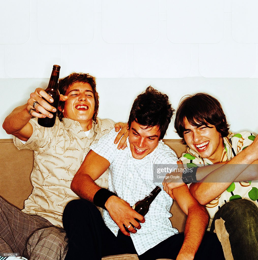 Three young men sitting on a couch holding beer bottles