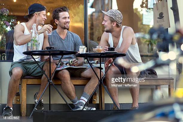 Three young men sitting outside cafe