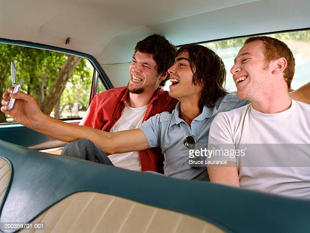 Three young men taking picture with camera phone in back seat of car