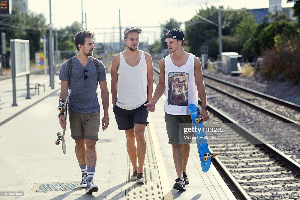 Three young men walk along train station platform