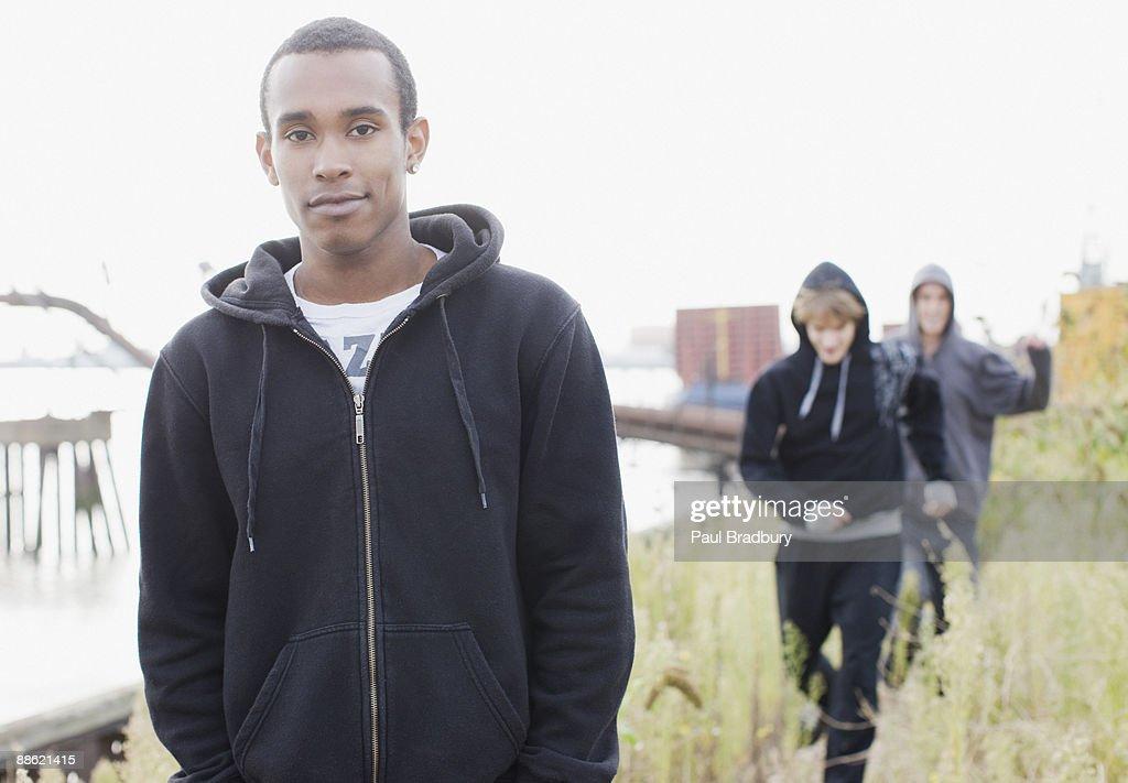 Three young men walking through urban field : Stock Photo