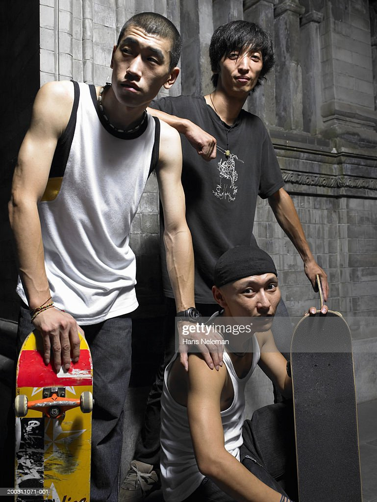 Three young men with skateboards, portrait, night : Stock Photo