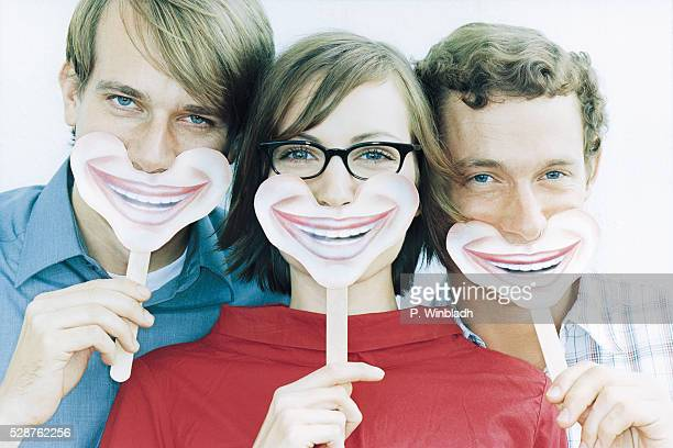 Three young people holding masks in front of their mouth
