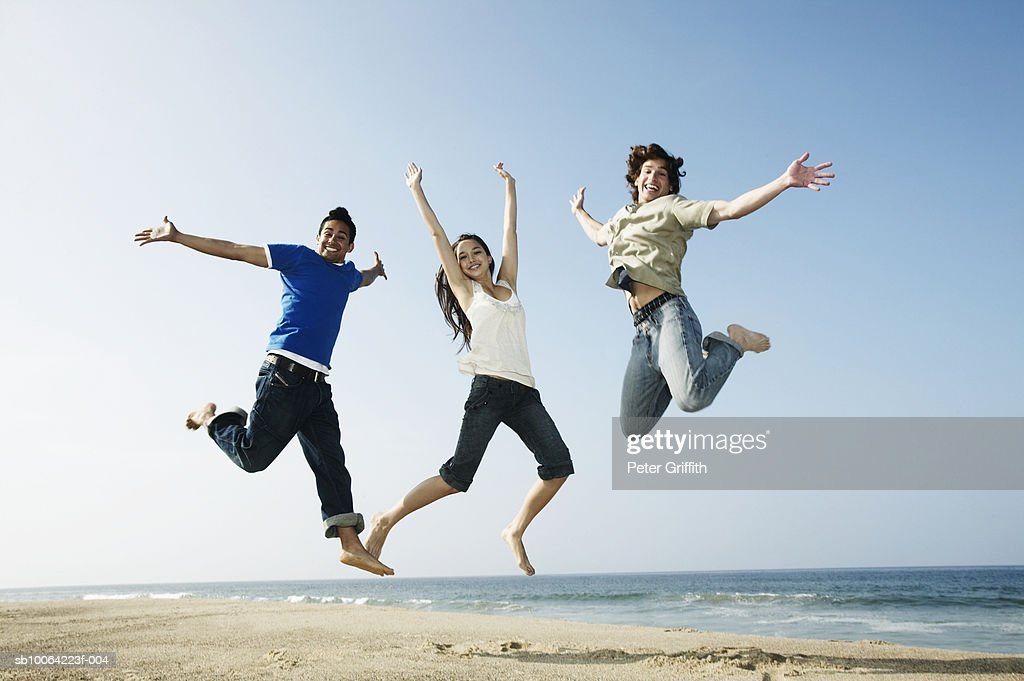 Three young people jumping mid-air on beach, portrait, low angle view : Stock Photo