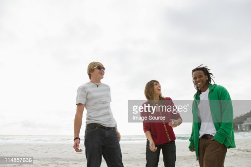 Three young people on beach : Stock Photo