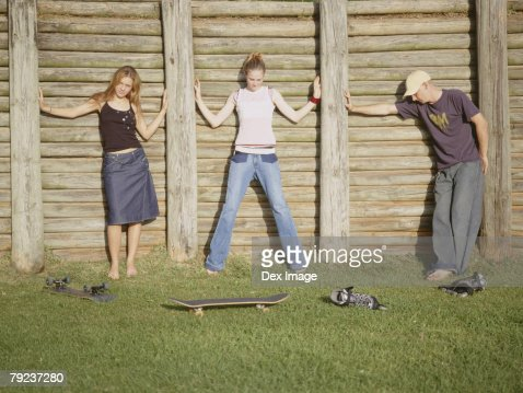 Three young people posing in front of wooden fence : Stock Photo