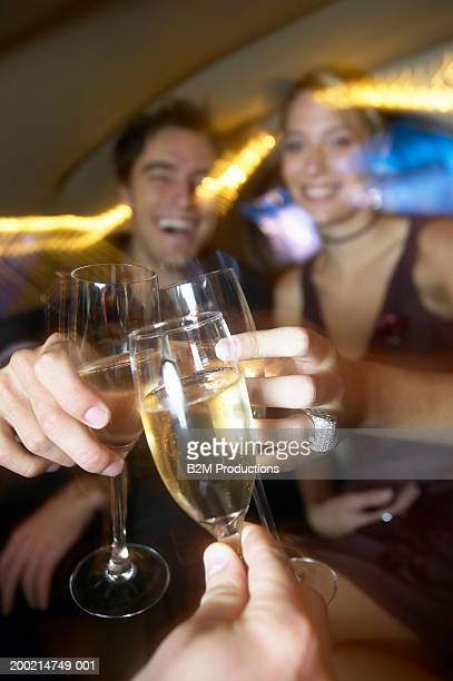 Three young people raising champagne flutes, close-up