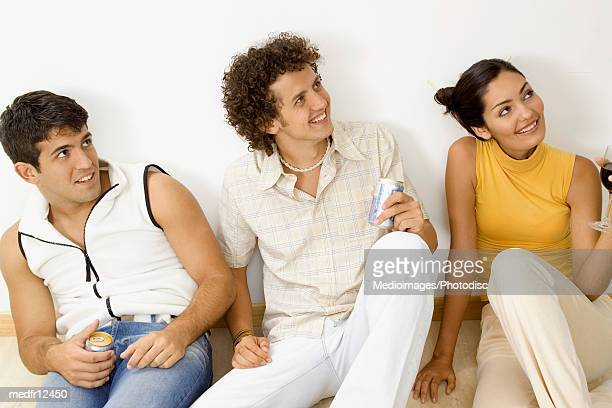 Three young people sitting on floor with drinks