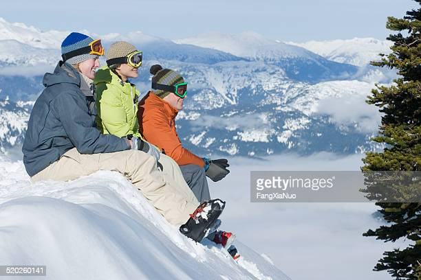 Three young people sitting on snow bank in mountain landscape