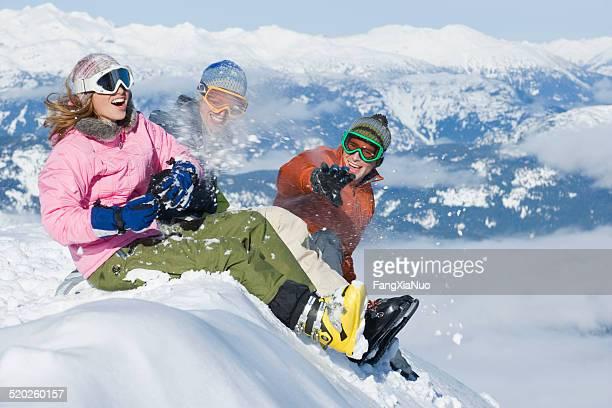 Trois jeunes assis sur la neige dans les montagnes paysage bank
