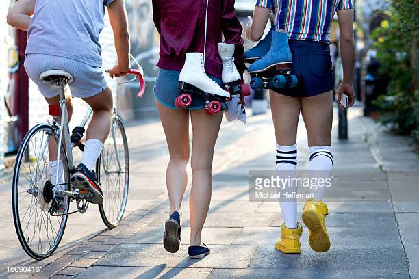 three young people walking and cycling