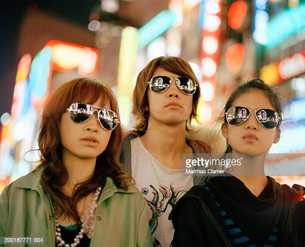 Three young people wearing sunglasses, signage reflected in glasses
