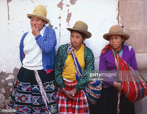 Three young peruvian woman leaning on a wall, Peru, Cusco