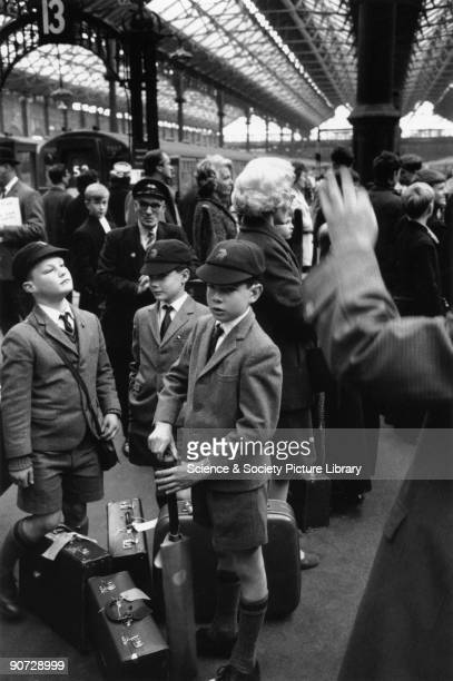 Three young schoolboys waiting with their luggage on a platform at Victoria railway station in London before returning to boarding school Photo taken...