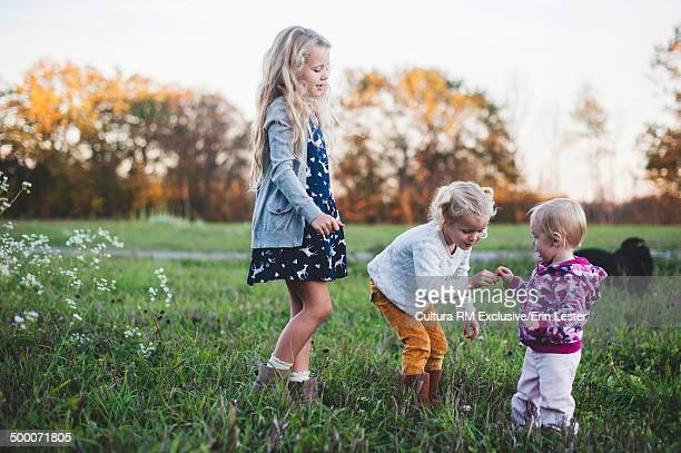 Three young sisters picking wildflowers in meadow