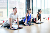 Three young sporty people doing plank exercise on yoga mat in fitness center.