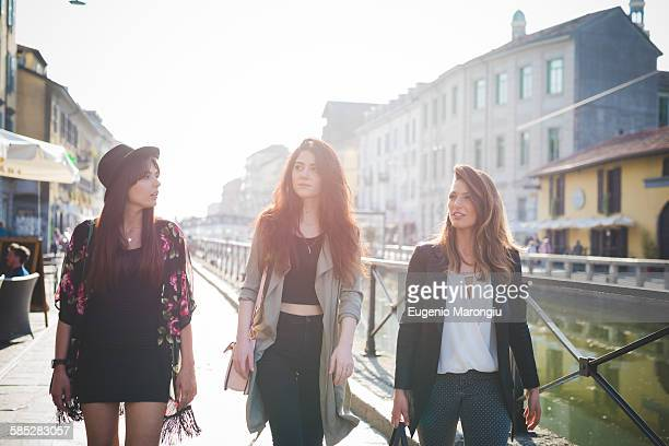 Three young stylish women strolling on canal waterfront
