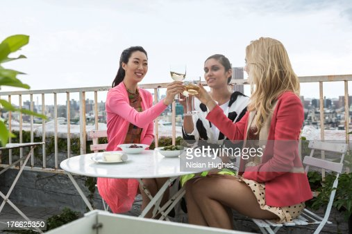 three young woman having a drink on city roof : Stock Photo