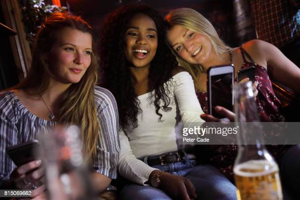 Three young woman in bar taking photo of themselves