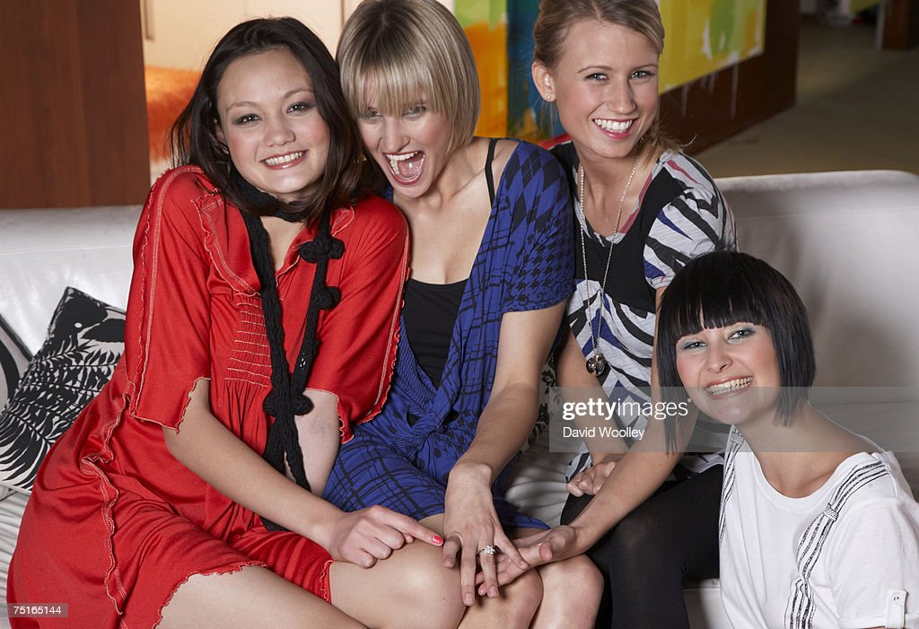 Three young women and teenage girl (16-17) sitting on sofa, laughing, portrait
