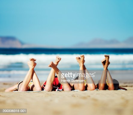 Three young women and young man lying on beach, feet in air : Stock Photo