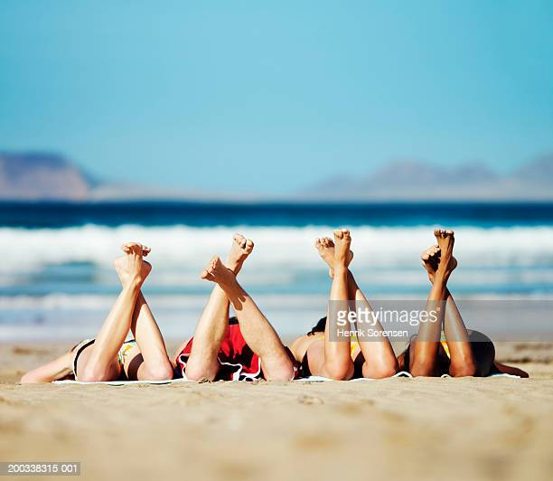 Three young women and young man lying on beach, feet in air