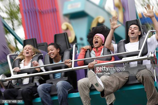 Three young women and young man on fairground ride, screaming