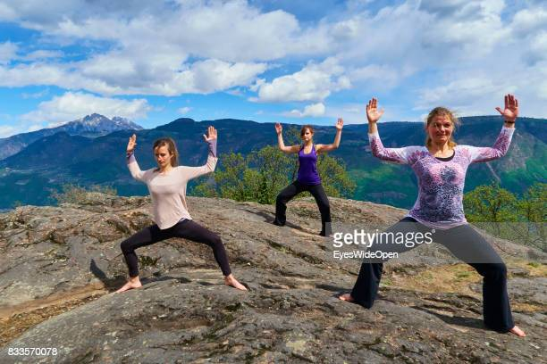 Three young women are practicing openair Yoga on a rock in the mountains of South Tyrol on April 21 2015 in Lana Italy