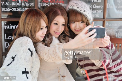 Three young women are taking photo on smartphone : Stock Photo