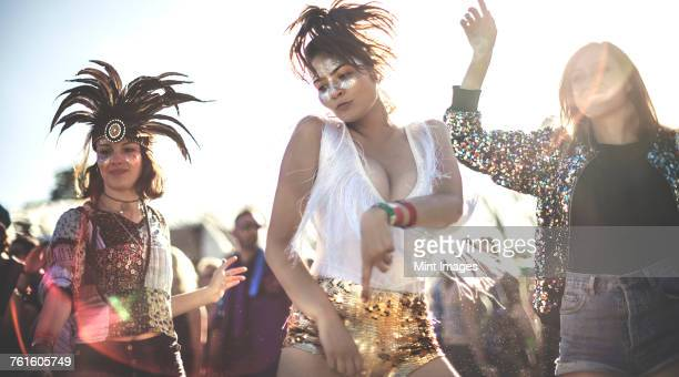 Three young women at a summer music festival wearing sequins and feather headdresses dancing among the crowd.