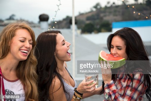 Three young women at barbeque with large slice of melon : Stock Photo