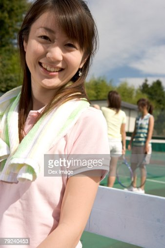 Three young women at tennis court : Stock Photo