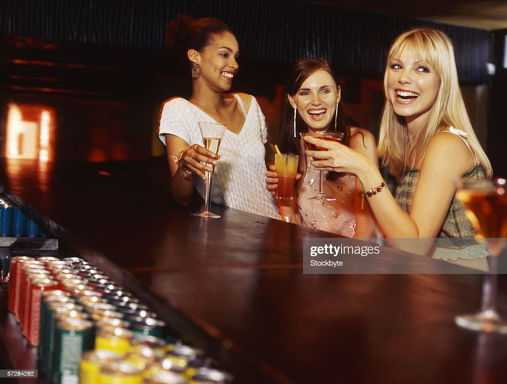 Three young women at the bar counter holding drinks : Stock Photo