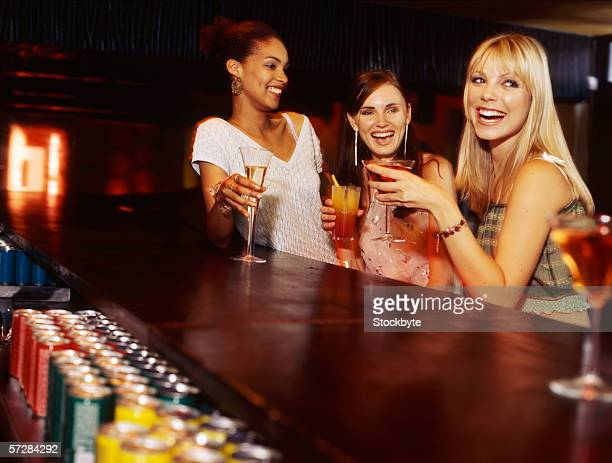 Three young women at the bar counter holding drinks